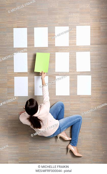 Businesswoman sitting on floor organizing blank sheets of paper