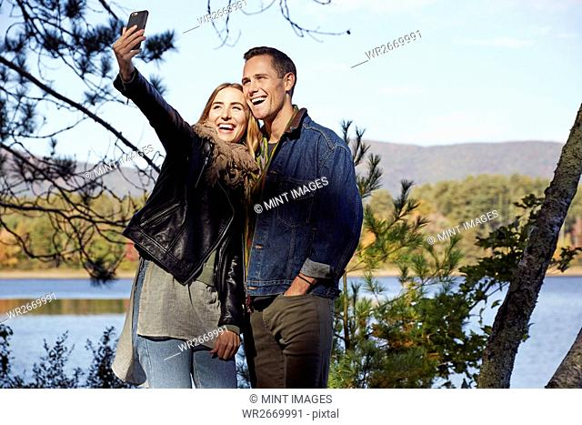 Two people, man and woman taking a selfie on the shore of a lake in autumn