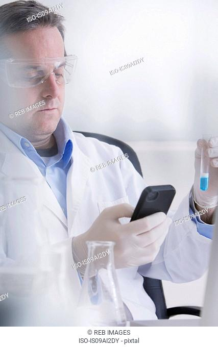 Scientist holding smartphone and test tube