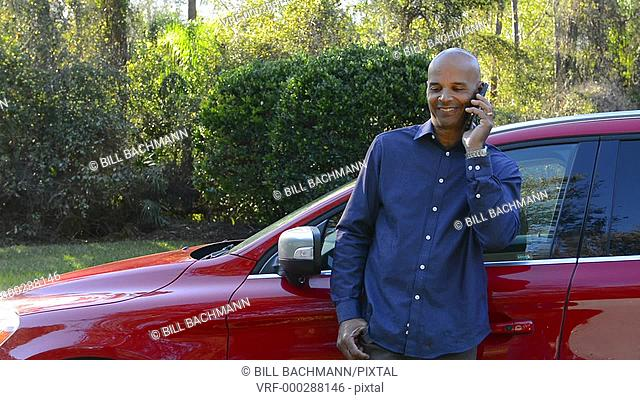 Black man Caribbean at home outside talking on cell phone business with red car Model Released, MR-16