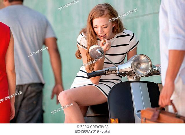 Young woman sitting on moped applying lipstick in city