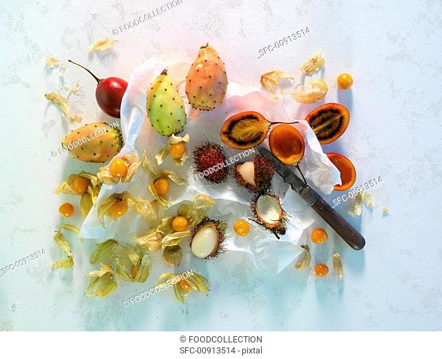 Tunas, tamarillos, lychees and star fruit on paper with a knife