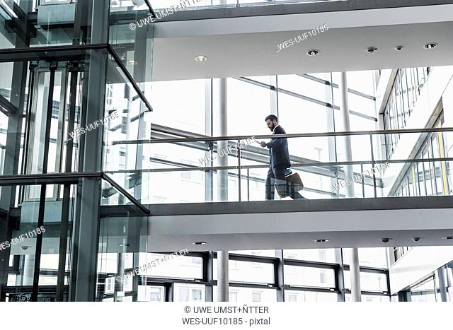 Businessman walking in office building, while using smart phone