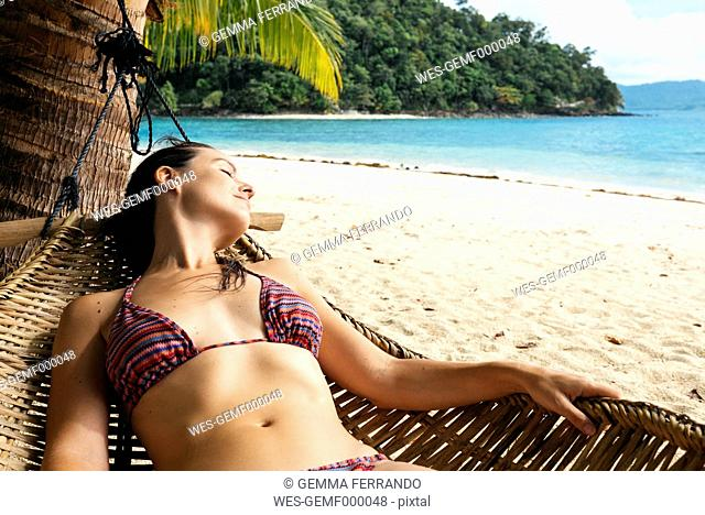 Philippines, Palawan, Woman relaxing on beach hammock