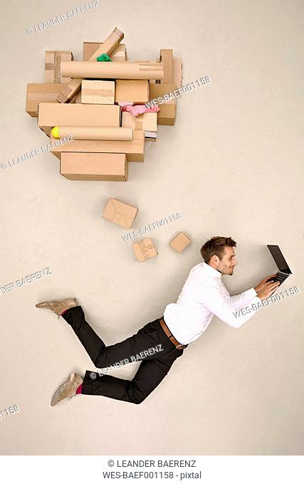 Flying businessman shopping online