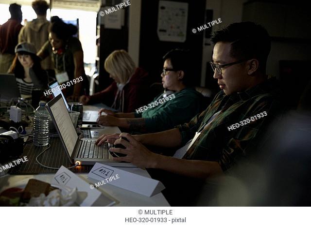 Focused hacker working hackathon at laptop in dark office