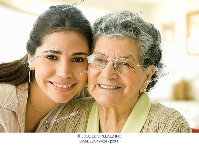 Hispanic grandmother and adult granddaughter hugging