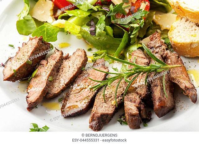 slices of a steak on fresh salad