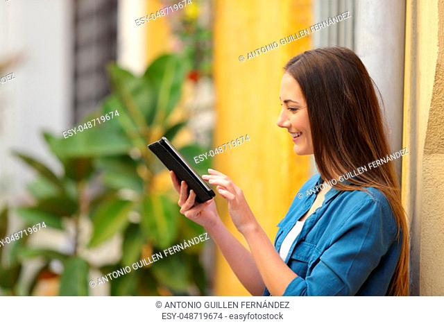 Side view of a happy woman using a tablet browsing online content in the street