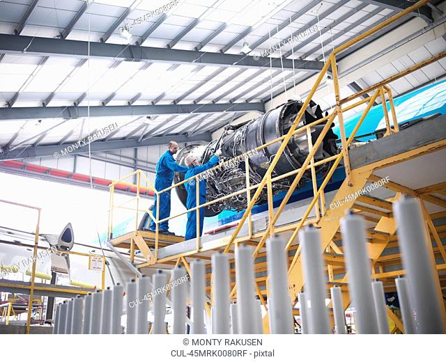 Workers examining airplane machinery