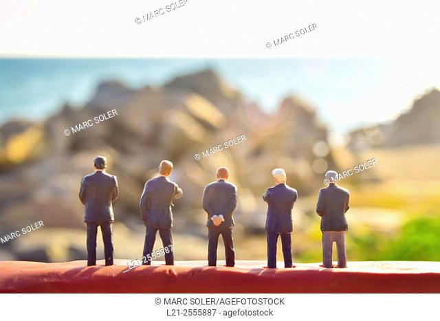 Figurines of businessmen watching a blurred landscape. Toy businessmen team, silhouettes of men against blurred seascape, rocks and sea