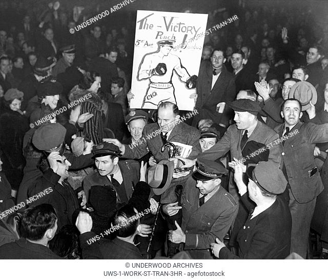 New York, New York: 1937 Members of the Transit Workers Union carry their international president, Michael J. Quill, up to the speakers' platform during a bus...