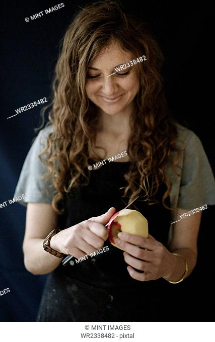 A woman in a blue apron peeling an apple with a knife