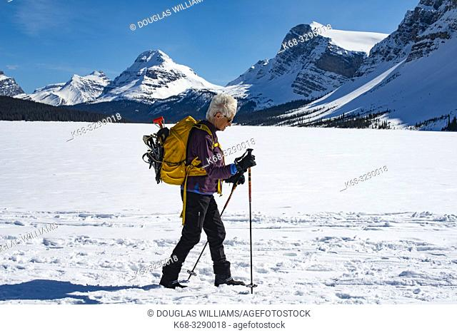 A woman, 71, skis on Bow Lake, in Banff National Park, Alberta, Canada, Rockies, Rocky Mountains