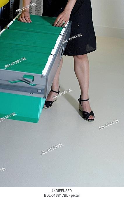legs of woman looking through files in filing cabinet