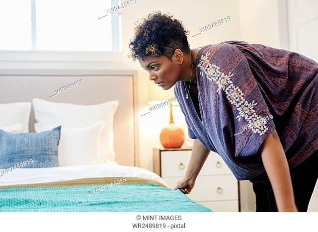 A woman smoothing a throw over a double bed in a bedroom