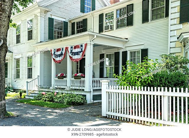 Woodstock, VT, USA. Partial View of a Traditional Colonial Attached Row House, Decorative, Patriotic Bunting Gracing the Front Porch