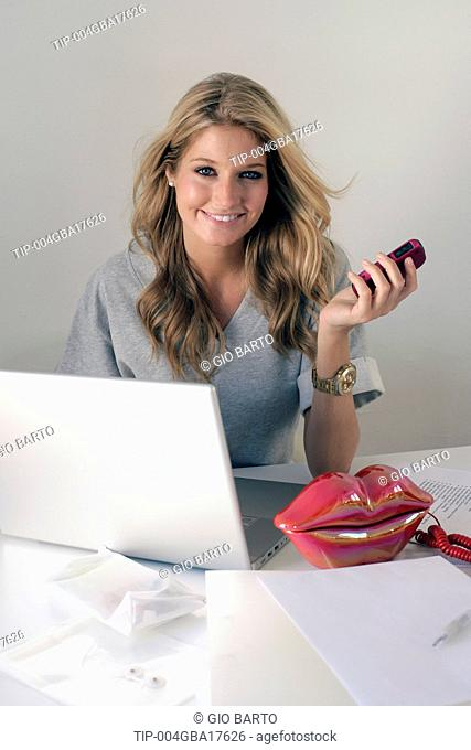 Young woman with laptop and telephone