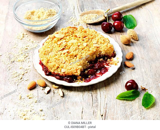 Sour cherry and almond crumble pudding, almonds, cherries, white washed rustic wooden table