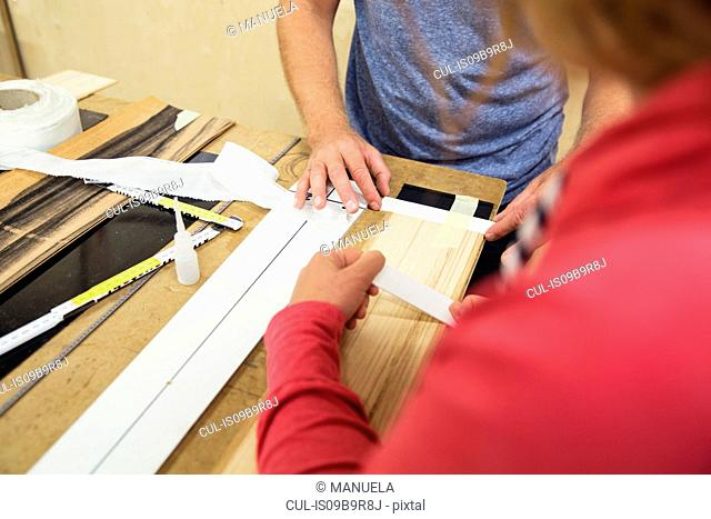 Man and woman in workshop, making ski equipment, mid section
