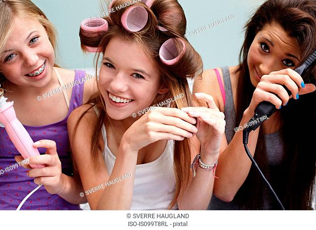 Teenage girls styling their hair