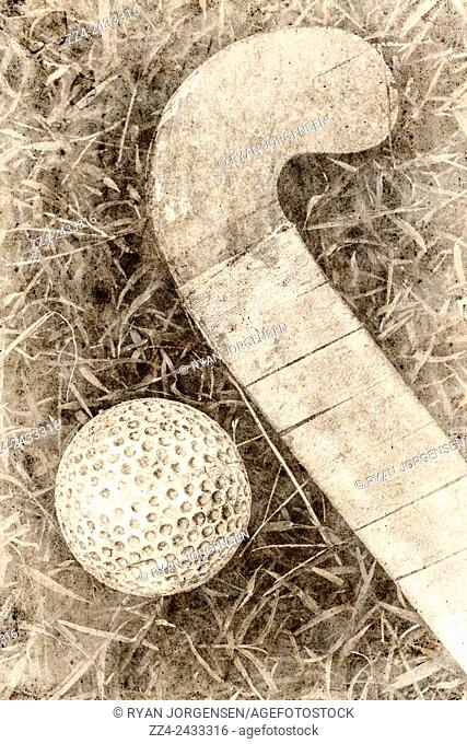 Traditional old paper photo of a taped up field hockey stick next to dimpled ball. Old-fashioned sport artwork