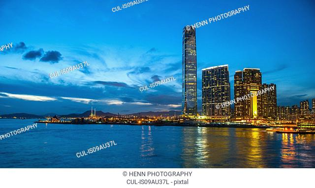 View from Victoria Harbor of skyline illuminated at night, Hong Kong, China