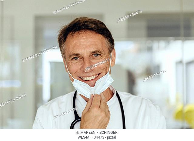 Portrait of a doctor, removing surgical mask, smiling