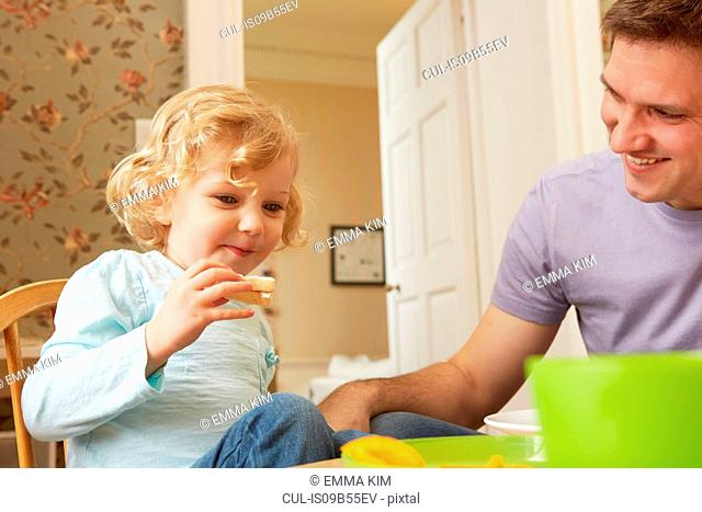 Mid adult man and toddler daughter eating bread at kitchen table