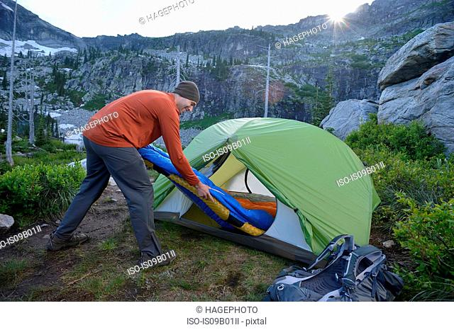 Man putting sleeping bag in tent at sunset, Fault Lake, Selkirk Mountains, Idaho