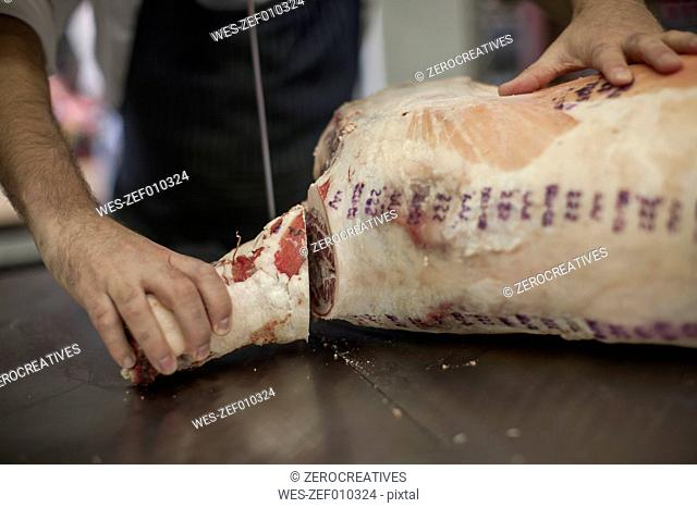 Butcher jointing carcass in butchery