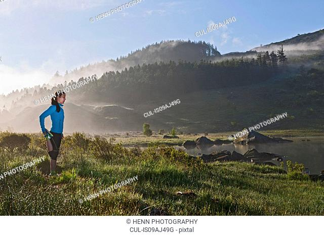 Female runner stretching by lake, Capel Curig, Snowdonia, North Wales, UK