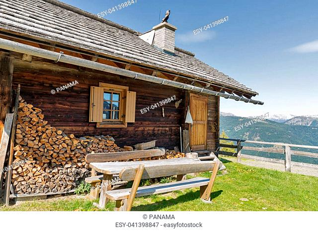 Front yard with wooden table of shepherd lodge on a highland pasture with Alpine mountain landscape in Western Carinthia, Austria
