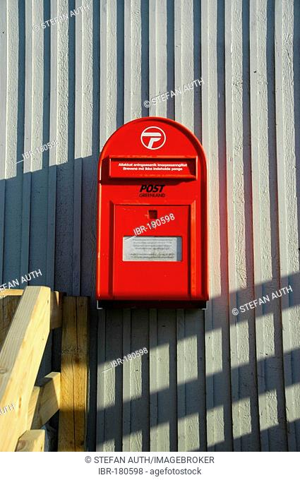 Red letter-box of Post Greenland at a wall in Ammassalik Eastgreenland