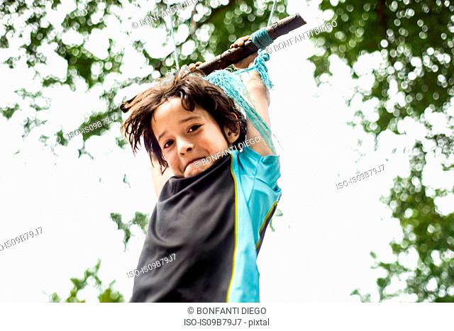 Young boy swinging on home-made swing in tree, low angle view