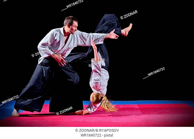 Fight between two aikido fighters on black
