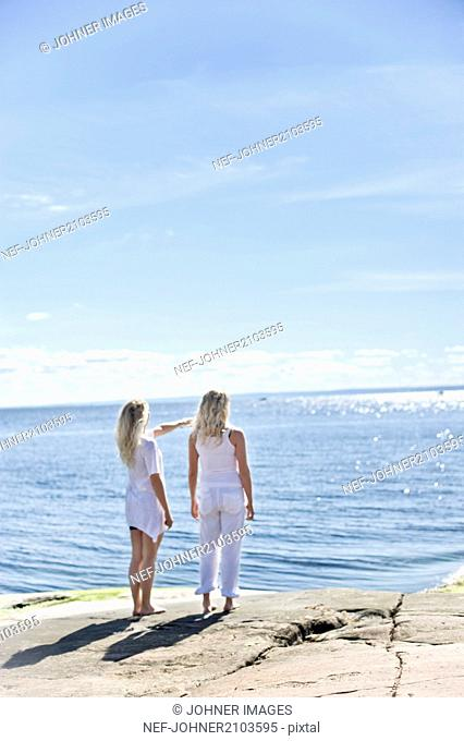 Young women standing and looking at sea
