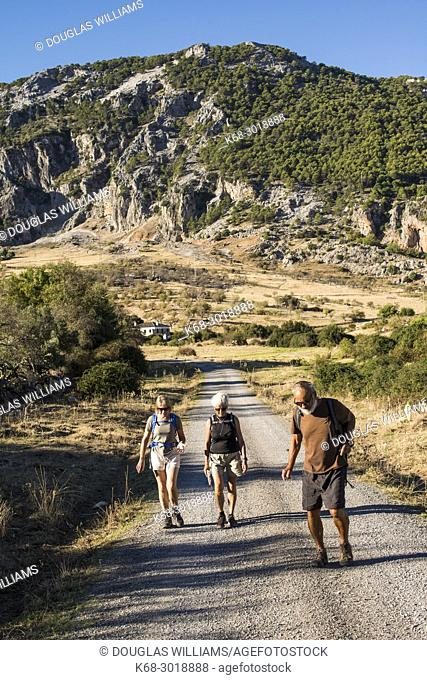Senior hikers on the road below the village of Grazalema, Cadiz province, Andalucia, Spain