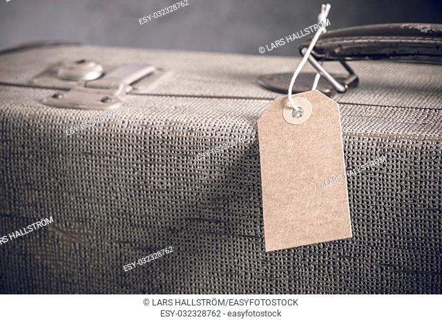 Blank name tag with copy space on old vintage suitcase. Concept of travel with luggage, tourism and holiday destination