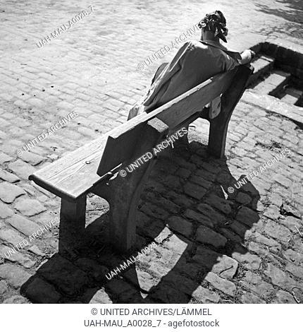 Junge Frau auf einer Bank, Deutschland 1930er Jahre. Young woman sitting on a bench, Germany 1930s