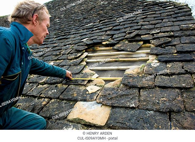 Roofer measuring hole in traditional stone tile roof