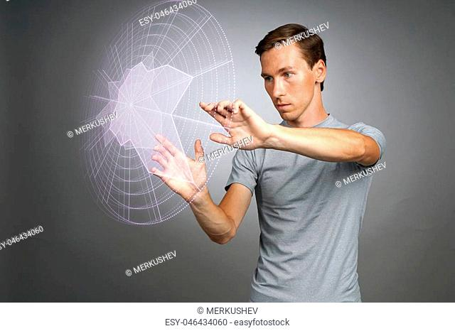 Young man working with interactive Sci-Fi HUD interface. High-tech concept