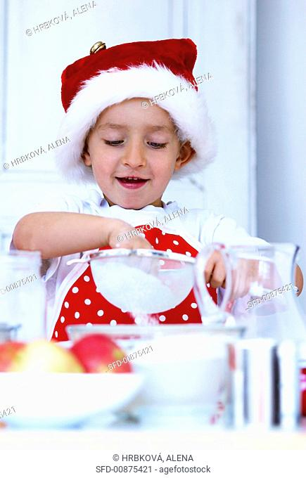 Small boy sieving flour