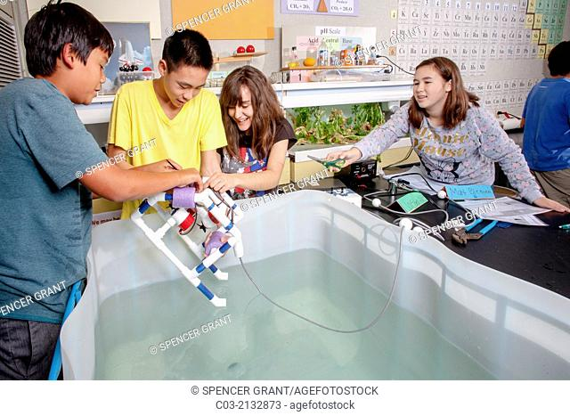 Using a laboratory tank, multiracial middle school students in Mission Viejo, CA, test the remote operated vehicle (ROV) they built in their robotics classroom
