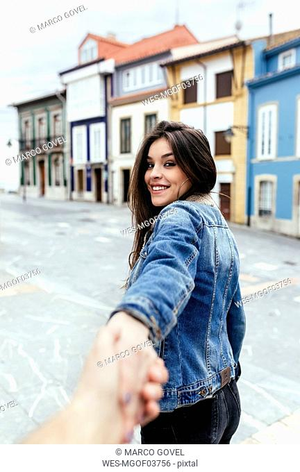 Portrait of a smiling brunette woman holding hand in a town