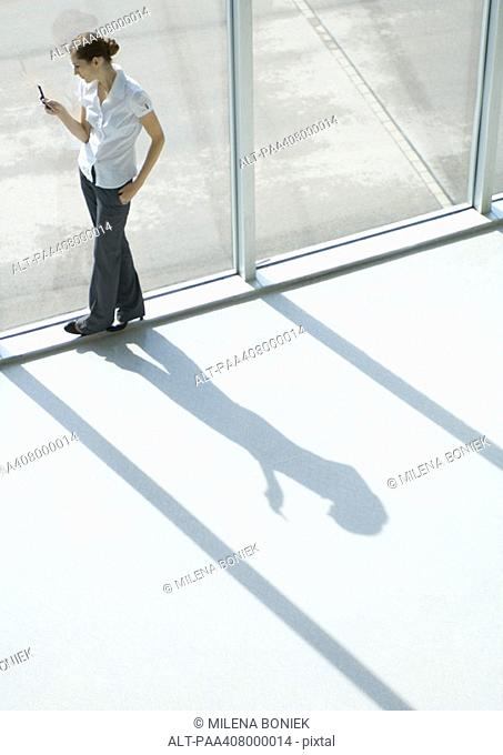 Woman using cell phone by window, full length, high angle view