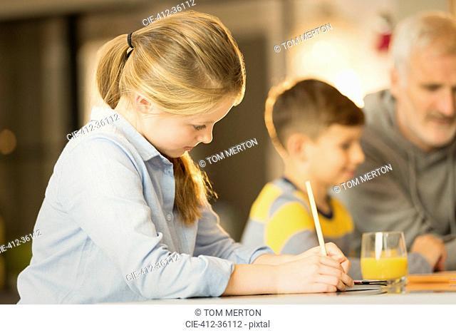 Girl doing homework at counter