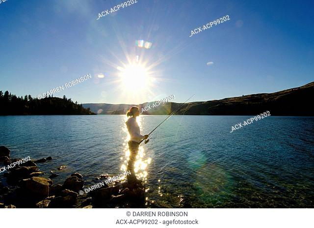 Young woman fishing on a beautiful autumn day on Kalamalka Lake in Vernon, in the Okanagan region of British Columbia, Canada. MR022