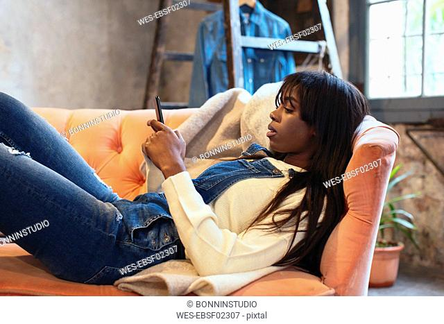 Young woman lying on the couch at home using cell phone