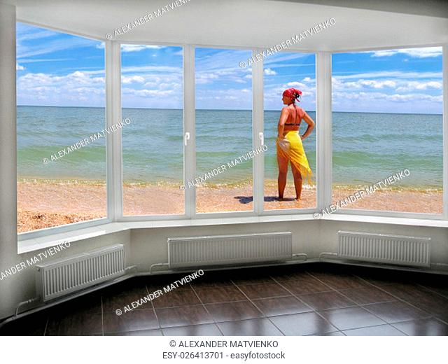 window with view to the sea and girl in pareo sunburnting at the seacoast